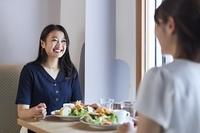 同僚と飲食店でランチを食べる日本人女性