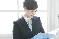 ファイルを確認する日本人ビジネスマン