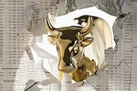 新聞の株式欄を破く牛の黄金像