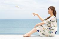 海辺で飛行機を飛ばす日本人女性