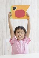 色画用紙で作った鯉のぼりを持つ日本人の男の子
