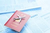 パスポートとミニチュア飛行機と英字新聞