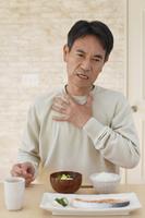 喉を押さえる中年日本人男性
