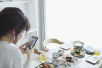 スマートフォンで写真を撮る日本人女性