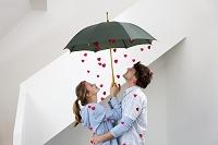 ハートが降る傘に一緒に入る外国人カップル