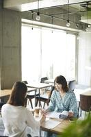 友達とカフェで話す日本人女性