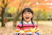 紅葉の公園で落ち葉で遊ぶ女の子