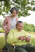 公園でスマートフォンを使用する老夫婦