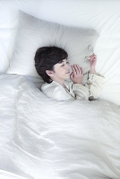 ベッドで眠るミドル女性