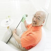 ゴルフクラブを磨く中高年の日本人男性