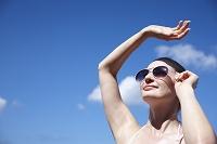 日差しを遮るサングラスをかけた女性
