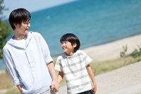 海辺を歩く日本人親子