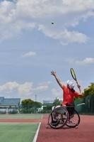 サーブを打つ車いすテニス選手