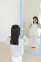 鏡の前で洋服をあてる女の子