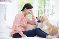 ソファに座る40代の日本人女性と犬