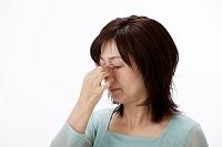 眼精疲労で眉間に手をやる中高年女性