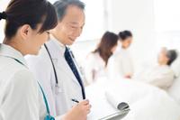 カルテに記入する看護師と医師