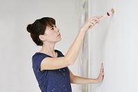 DIYで壁を塗る女性