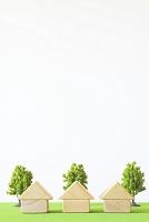 芝生に置かれた積み木の家とミニチュアの木