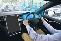 自動運転車を運転する男性の手元