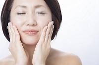 両頬に手をあてるミドル日本人女性