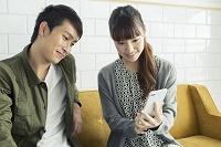 一つのスマートフォンを一緒に眺める20代男女