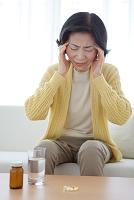こめかみを押さえる中高年日本人女性