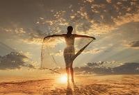 夕暮れの空に腕を広げて立つ女性