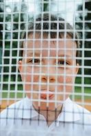 テニスラケットに隠れる男の子