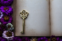 花に囲われたアンティーク本と鍵