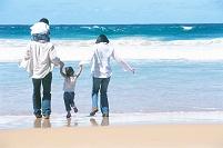波打ち際で遊ぶ日本人家族