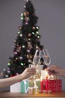 クリスマスツリーとプレゼントとキャンドルとシャンパンで乾杯す...