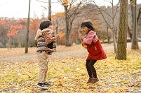 落ち葉の公園でジャンプする日本人の子供