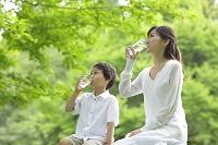 新緑の中で水を飲むお母さんと男の子