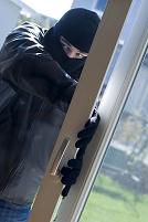 家のサッシから侵入する犯罪者