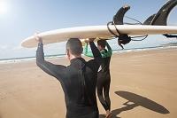 サーフボードを運んでいる男性