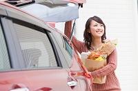 トランクから出した買い物袋を持つ日本人女性
