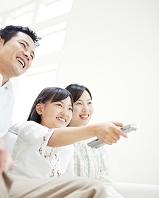 リモコンを操作する娘と両親