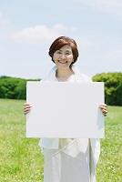新緑とホワイトボードを持つ日本人のシニア女性