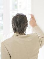 窓の外を見つめるシニア男性の後ろ姿
