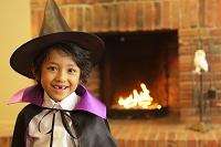暖炉の前でハロウィンの仮装をする男の子