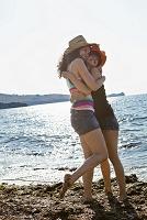 夕方の海辺で抱き合う外国人女性