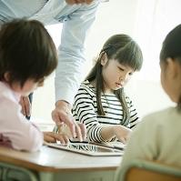 授業でタブレットを操作する小学生