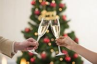 クリスマスツリーと乾杯するシャンパングラスと手