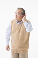 耳をすますシニアの日本人男性