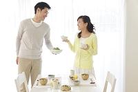 朝食を並べる主婦並べる新婚日本人夫婦