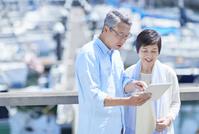 タブレットを見る日本人シニア夫婦