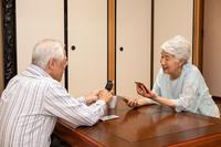 携帯電話とスマホを操作する日本人シニア夫婦