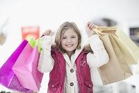 両手いっぱいにショッピングバッグを持つ外国人の女の子