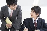 勉強する男子中学生と指導する講師